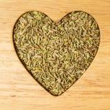 茴香莳萝种子心形在木板 库存图片