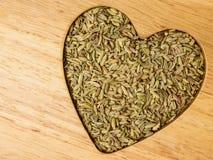 茴香莳萝种子心形在木板 免版税库存图片