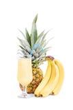 香蕉、菠萝和一杯汁液 免版税库存照片