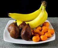 香蕉、Salak和柑桔在白色板材结果实 库存图片
