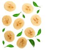 香蕉切了用在与拷贝空间的白色背景隔绝的绿色叶子装饰您的文本的 顶视图 平的位置 免版税图库摄影