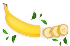 香蕉切了用在白色背景隔绝的绿色叶子装饰 顶视图 平的位置 免版税库存图片