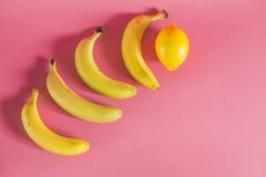 香蕉和柠檬在桃红色背景 免版税库存图片
