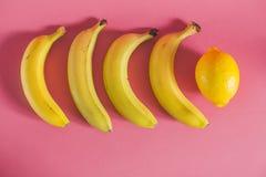香蕉和柠檬在桃红色背景 免版税库存照片