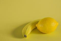 香蕉和柠檬在黄色背景 免版税库存照片