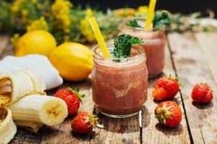 香蕉和草莓圆滑的人 在玻璃的两名冷的草莓香蕉圆滑的人与在厨房用桌上的成份 草莓巴娜 免版税库存照片