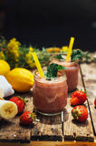 香蕉和草莓圆滑的人 在玻璃的两名冷的草莓香蕉圆滑的人与在厨房用桌上的成份 草莓巴娜 图库摄影