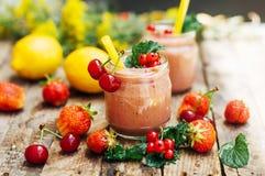 香蕉和草莓圆滑的人 在玻璃的两名冷的草莓香蕉圆滑的人与在厨房用桌上的成份 草莓巴娜 免版税图库摄影