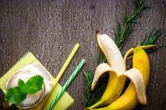 香蕉圆滑的人和新鲜的香蕉在木桌上 库存图片