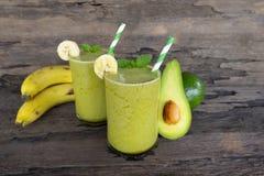 香蕉汁和鲕梨圆滑的人和绿色汁液喝在一块玻璃的健康,可口口味在木背景的减重的 免版税库存照片