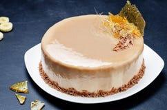 香蕉焦糖与牛奶巧克力釉的奶油甜点蛋糕 免版税库存照片