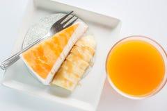 香蕉焦糖绉纱蛋糕和橙汁顶视图在白色 免版税库存图片