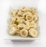 香蕉片断在白色板材的 免版税库存照片