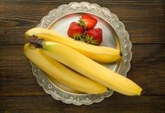 香蕉用在葡萄酒板材顶视图的草莓 库存图片