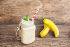 香蕉鸡尾酒和新鲜的香蕉在老木背景 免版税库存图片