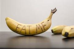 香蕉,在果皮他们中的一个被写了词吃我 免版税库存照片