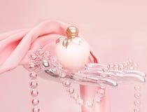 香水、一串小珠和桃红色丝绸围巾位于p 库存照片
