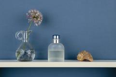 香水和花瓶有一朵花的在白色架子在蓝色墙纸 免版税库存图片