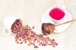 香水月季疏散的,热的茶和干玫瑰色花在木选项 库存照片