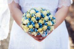 香水月季美丽的婚礼花束与蓝色丝带的在新娘的手上,特写镜头,水平顶视图 免版税库存照片