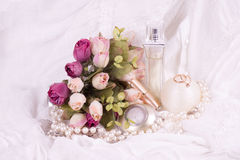 香水瓶、白色玫瑰和珍珠小珠 免版税图库摄影
