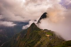 马丘比丘由来自开头云彩的第一阳光照亮了 印加人` s城市是被参观的旅行des 库存照片