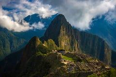 马丘比丘由来自开头云彩的第一阳光照亮了 印加人` s城市是被参观的旅行des 图库摄影