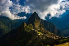 马丘比丘由来自开头云彩的阳光照亮了 印加人` s城市是被参观的旅行目的地我 免版税库存图片