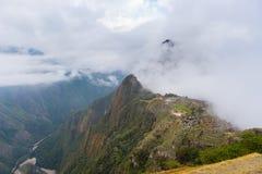 马丘比丘由来自开头云彩的第一阳光照亮了 印加人` s城市是被参观的旅行des 免版税库存照片