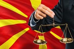 马其顿法官拿着正义金黄标度有马其顿挥动的旗子背景 平等题材和法律概念 免版税库存图片
