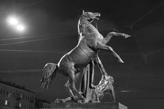马和下落的人 夜雕刻的构成 库存图片
