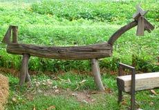马在鲜绿色的植物园里塑造了棕色长木凳 免版税图库摄影