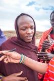 年轻马塞语帮助他的朋友签署我的式样发行 库存照片