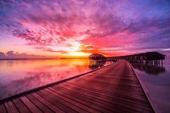 马尔代夫海岛日落风景 五颜六色的云彩和天空与豪华水别墅和长的木码头 库存图片