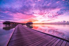 马尔代夫海岛日落风景 五颜六色的云彩和天空与豪华水别墅和长的木码头 免版税图库摄影