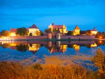 马尔堡城堡在与反射的夜之前在Nogat 图库摄影