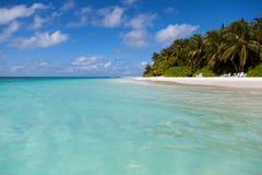 马尔代夫、看法从水到海岛有棕榈滩的和蓝天 免版税库存照片