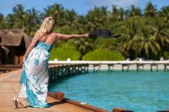 马尔代夫,投掷她的帽子的妇女入水 免版税图库摄影