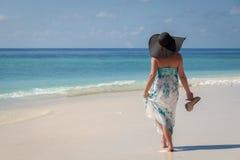 马尔代夫,走沿与sunhat的海滩和在手上的高跟鞋的少妇 免版税库存照片
