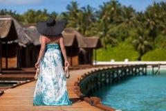 马尔代夫,走沿有高跟鞋的桥梁的少妇在手和黑帽会议上 免版税库存图片