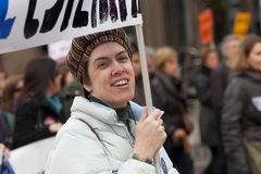 微笑的妇女在马德里拿着抗议横幅 免版税图库摄影
