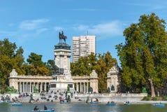 马德里Retiro公园池塘&纪念碑 人休闲在步的阳光下和在明轮船 库存照片