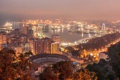 马拉加在与港口和船和光线范围的晚上 免版税库存图片