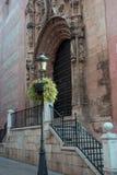 马拉加,西班牙大教堂  老石墙视域、门和台阶 以为背景的黑伪造的街灯 免版税库存照片