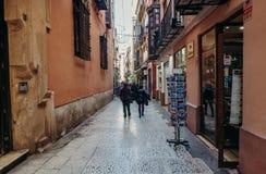 马拉加,西班牙- 2017年12月5日, :狭窄的街道在马拉加市的历史的市中心有走在商店附近的步行者的 库存照片