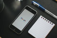 马拉加,西班牙- 2018年3月6日:在一个手机屏幕的谷歌app,安置在与其他办公室材料的一个黑工作区 免版税图库摄影