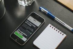 马拉加,西班牙- 2018年3月6日:有埃洛的app手机屏幕的,安置在有办公室材料的一张黑书桌 免版税库存照片