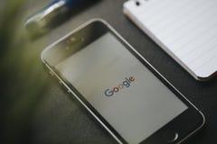 马拉加,西班牙- 2018年3月6日:谷歌app宏观细节在一个手机屏幕的,安置在与其他材料的一个黑工作区 库存图片