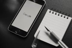 马拉加,西班牙- 2018年3月6日:谷歌app的黑白图象在一个手机屏幕的,安置在一个黑工作区 库存图片