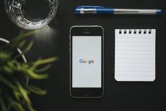 马拉加,西班牙- 2018年3月6日:谷歌app顶视图在一个手机屏幕的,安置在与办公室材料的一个黑工作区 库存照片